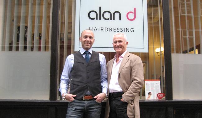 Alan d founder Alan Hemmings & director Edward Hemmings in front of the alan d logo.