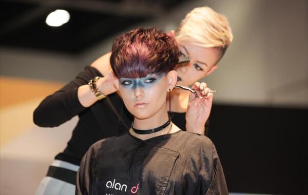 Alan d hairdressing student cutting a womans short auburn hair.