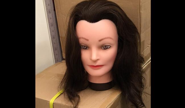 Hairdressing dummy head with dark brown hair.