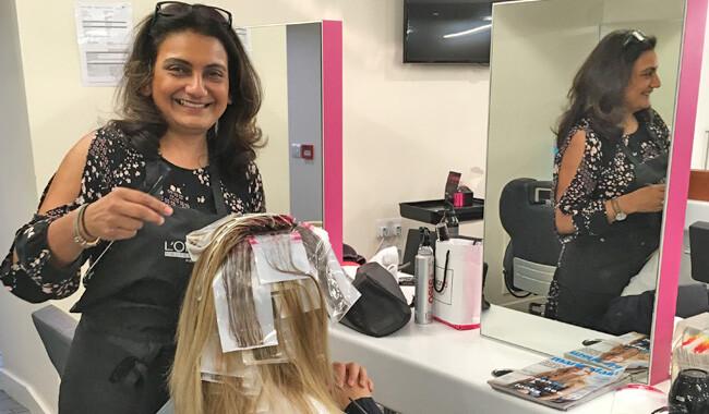 Alan d hairdressing teacher Sejal putting highlights in a womans hair.
