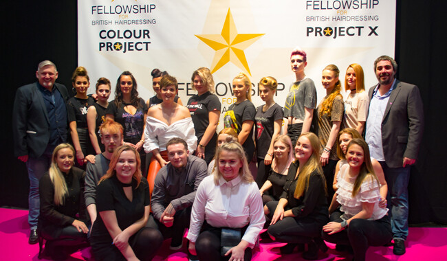 Alan d students and staff in front of fellowship backdrop at Salon International.