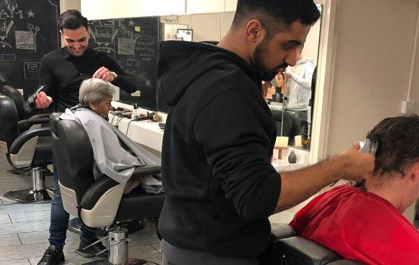 Two men having their hair trimmed by Alan d barbering apprentices.